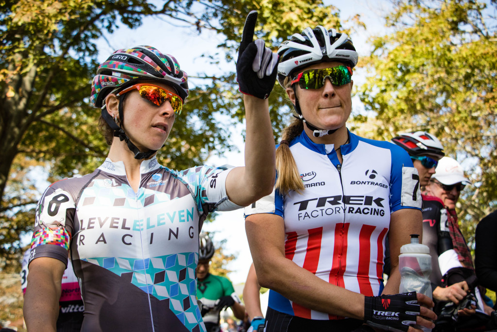 At the start line, Arley Kemmerer (Level Eleven Racing) and Katie Compton (Trek Factory Racing) gesticulate/discuss the start chute and where it drops riders onto the course. © 2015 John Kavouris