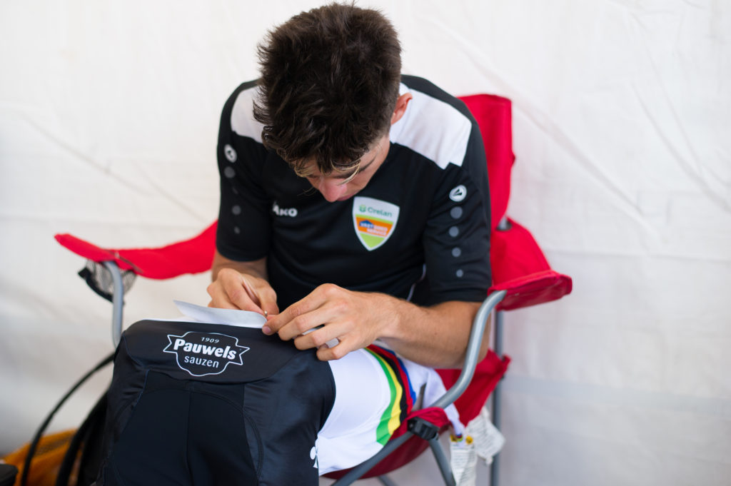 Wout van Aert sitting in a camping chair in a tent pinning his numbers. On his rainbow jersey. © 2016 Ethan Glading