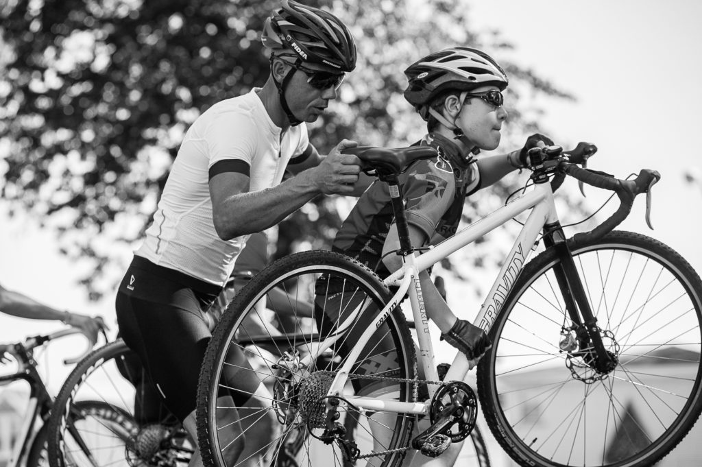 Nys assists a young rider with picking up and shouldering his bike. © 2016 Ethan Glading