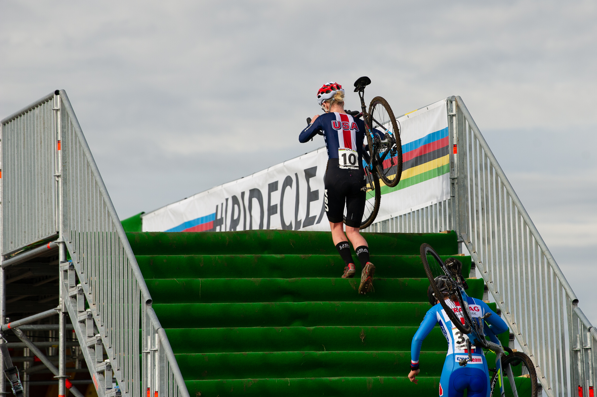 Cassidy Hickey carries her bike at the UCI Cyclocross World Championships