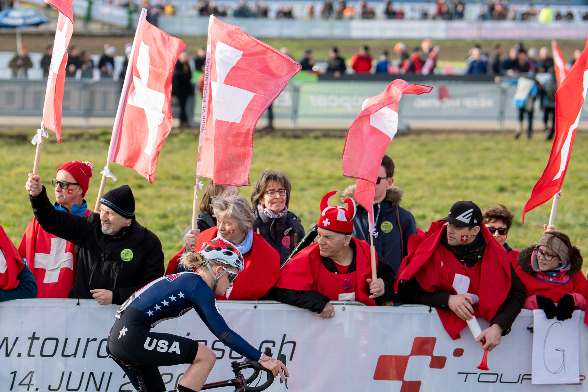 Cassidy Hickey rides by a group of Swiss fans at the UCI Cyclocross World Championships