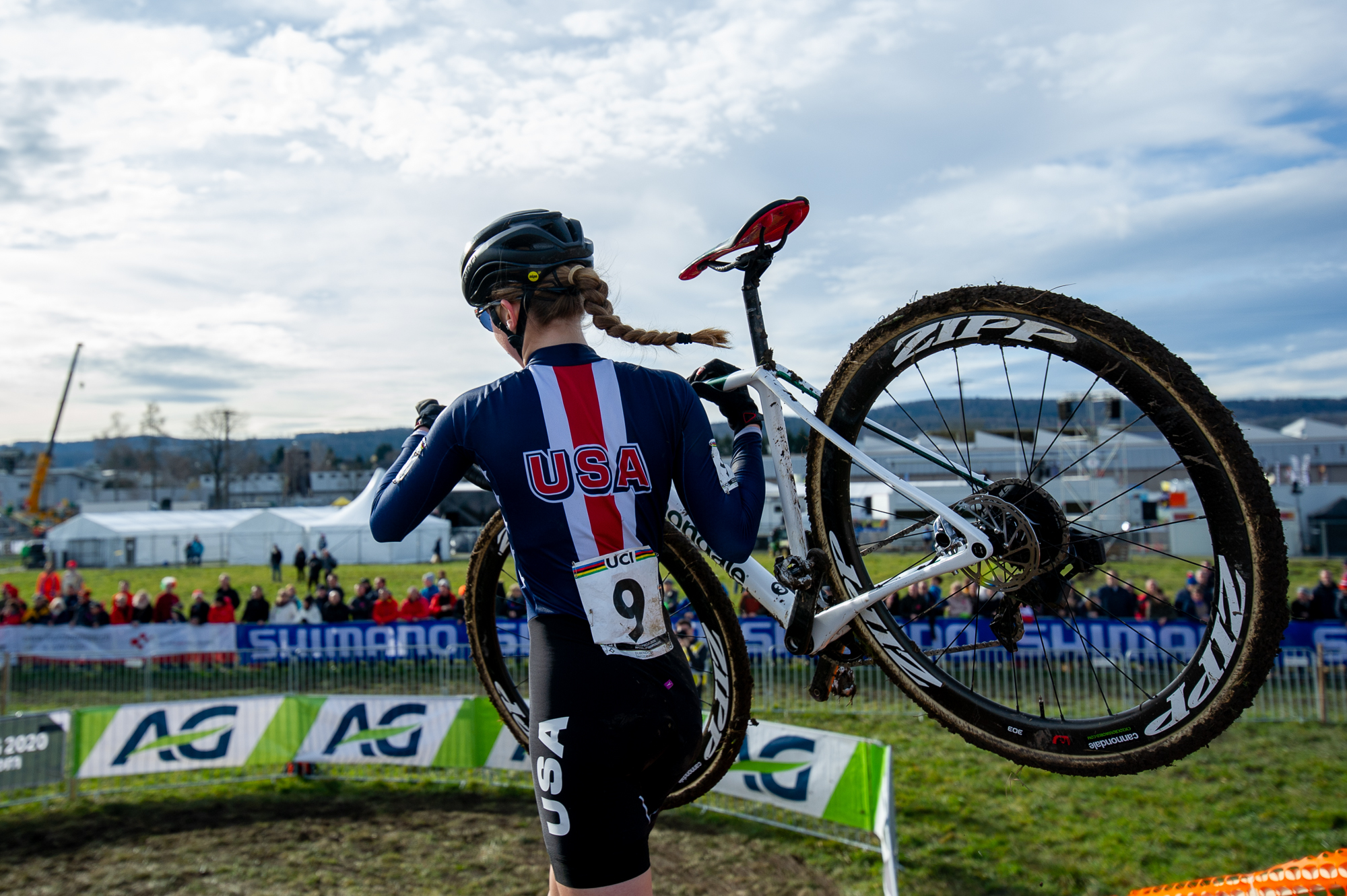 Lizzy Gunsalus shouldering her bike at the UCI Cyclocross World Championships